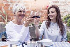 Seduta del vino dell'assaggio della figlia dell'adulto e della madre all'aperto Fotografia Stock