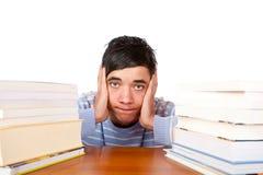 Seduta dell'allievo maschio frustrata fra i libri Immagini Stock