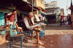 Seduta dell'anziano all'aperto e leggere un giornale indiano sulla via Immagini Stock