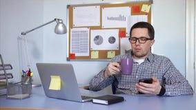 Seduta dell'impiegato di concetto e smartphone usando Prende una rottura e beve il caffè video d archivio