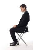 Seduta dell'uomo d'affari e compressa usando immagini stock