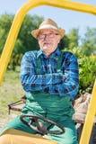 Seduta dell'uomo senior fiera in suo trattore dopo la coltivazione della sua azienda agricola Fotografia Stock Libera da Diritti