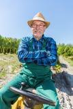 Seduta dell'uomo senior fiera in suo trattore dopo la coltivazione della sua azienda agricola Fotografie Stock