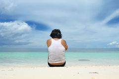 Seduta dell'uomo sola sulla spiaggia Immagini Stock