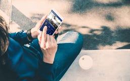 Seduta della donna e controllo domestico astuto app di uso sul telefono cellulare e fotografia stock libera da diritti