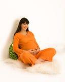 Seduta della donna incinta Immagine Stock