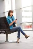 Seduta della donna più anziana e telefono cellulare attraenti usando Fotografia Stock