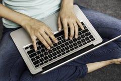 Seduta della giovane donna mentre per mezzo del computer portatile Fotografia Stock