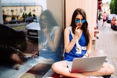 Seduta della ragazza all'aperto con caffè in occhiali da sole Fotografia Stock
