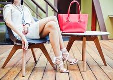 Seduta della ragazza del caffè di estate con grandi borse alla moda eccellenti rosse in brevi vestito e tacchi alti bianchi su un Fotografia Stock