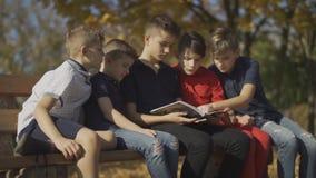 Seduta della società dei ragazzi sul banco e guidare una rivista Gli amici spendono la rivista di guida di tempo un giorno solegg archivi video