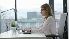 Seduta di Bisinesswoman e per mezzo di un computer portatile all'interno Immagine Stock Libera da Diritti