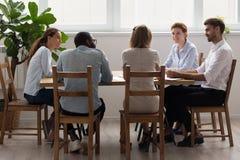 Seduta di conversazione del diverso dell'ufficio gruppo di affari alla tavola in sala del consiglio fotografia stock libera da diritti