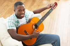 Seduta di distensione del giovane sul sofà che gioca chitarra Fotografia Stock