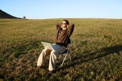 Seduta di distensione dell'uomo nel campo con il computer portatile Fotografie Stock