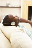Seduta di distensione dell'uomo sul sofà che ascolta la musica Fotografia Stock