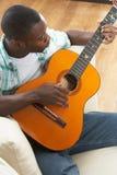 Seduta di distensione dell'uomo sul sofà che gioca chitarra Immagine Stock Libera da Diritti