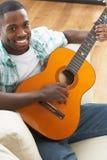 Seduta di distensione dell'uomo sul sofà che gioca chitarra Immagine Stock