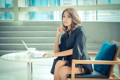 Seduta di lavoro dell'imprenditore femminile ad uno scrittorio Fotografie Stock