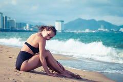 Seduta di modello del giovane bello bikini castana sexy sulla spiaggia del mare Viaggio del paese e concetto esotici di resto Fotografie Stock Libere da Diritti