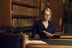 Seduta di modello femminile allo scrittorio ed al libro di lettura alla biblioteca Immagine Stock Libera da Diritti