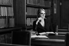 Seduta di modello femminile allo scrittorio ed al libro di lettura alla biblioteca Fotografia Stock