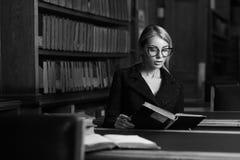 Seduta di modello femminile allo scrittorio ed al libro di lettura alla biblioteca Immagini Stock Libere da Diritti