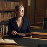Seduta di modello femminile allo scrittorio ed al libro di lettura alla biblioteca Fotografia Stock Libera da Diritti