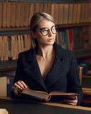 Seduta di modello femminile allo scrittorio ed al libro di lettura alla biblioteca Fotografie Stock Libere da Diritti
