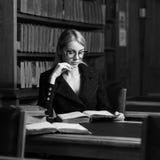 Seduta di modello femminile allo scrittorio ed al libro di lettura alla biblioteca Fotografie Stock