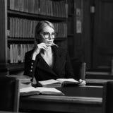 Seduta di modello femminile allo scrittorio ed al libro di lettura alla biblioteca Immagini Stock