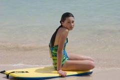 Seduta di modello su una scheda all'oceano Immagini Stock