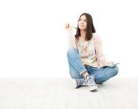 Seduta di pensiero del bello adolescente della ragazza sul pavimento. Fotografia Stock