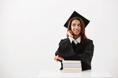 Seduta di pensiero sorridente laureata della ragazza africana vaga con i libri sopra fondo bianco Fotografia Stock Libera da Diritti