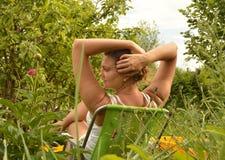 Seduta di riposo della giovane donna di retrovisione su una sedia nel giardino e tenersi per mano dietro la sua testa fotografia stock libera da diritti