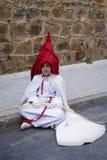 Seduta di riposo penitente sulla terra durante la processione di Pasqua fotografia stock