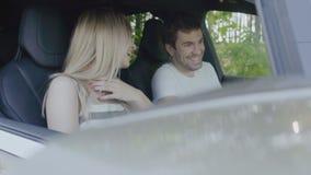 Seduta di risata delle giovani coppie in automobile moderna video d archivio