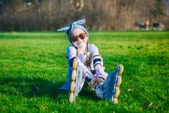 Seduta divertente della ragazza riccia sveglia nei pattini di rullo e negli occhiali da sole e nell'esame della macchina fotograf immagine stock libera da diritti