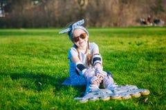 Seduta divertente della ragazza riccia sveglia nei pattini di rullo e negli occhiali da sole e nell'esame della macchina fotograf fotografia stock