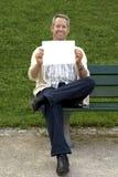 Seduta e holding di Babyboomer un segno in bianco Immagine Stock Libera da Diritti