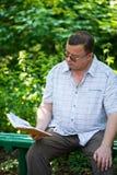 seduta e lettura dell'uomo Fotografia Stock