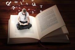 Seduta e lettura dell'uomo dentro il libro Immagini Stock