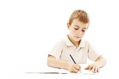 Seduta e scrittura del ragazzo di banco in taccuino Fotografia Stock