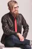 Seduta e sorridere dell'uomo di modo Fotografie Stock