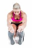 Seduta ed allungamento dell'atleta femminile Fotografia Stock Libera da Diritti