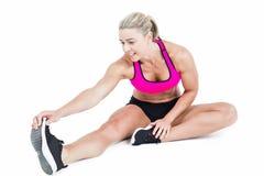 Seduta ed allungamento dell'atleta femminile Fotografie Stock