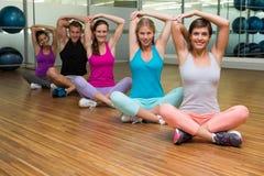 Seduta ed allungamento della classe di forma fisica Fotografia Stock