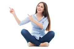 Seduta ed indicare della giovane donna Immagine Stock