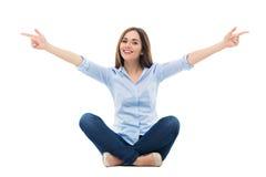 Seduta ed indicare della giovane donna Immagini Stock Libere da Diritti