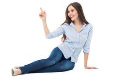 Seduta ed indicare della giovane donna Fotografia Stock